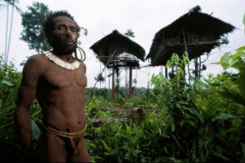 Представитель племени короваи на фоне своего жилища